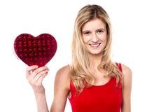 La ragazza teenager sorridente che mostra il cuore modella il regalo alla macchina fotografica Fotografie Stock