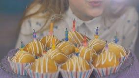 La ragazza teenager spegne le candele sui dolci del dolce sul suo compleanno stock footage