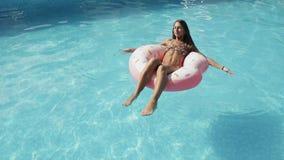 La ragazza teenager sta sedendosi in anello gonfiabile rosa, galleggiante su uno stagno nel parco dell'acqua nel giorno di estate stock footage