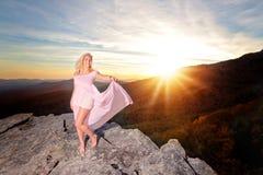 La ragazza teenager su una roccia trascura nelle montagne fotografia stock libera da diritti