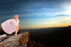 La ragazza teenager su una roccia trascura nelle montagne fotografie stock