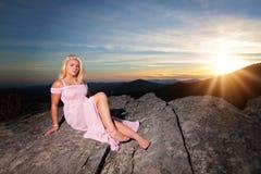 La ragazza teenager su una roccia trascura nelle montagne immagine stock libera da diritti