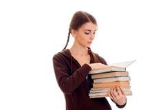 La ragazza teenager sveglia con le trecce tiene molti libri Immagine Stock
