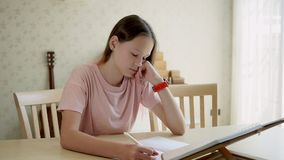 La ragazza teenager sveglia della ragazza esamina un libro e scrive in un taccuino poi esamina il suo orologio Concetto di Homesc stock footage