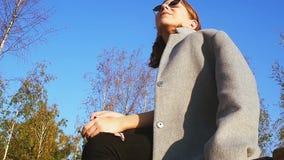 La ragazza teenager in un cappotto grigio mette sopra gli occhiali da sole e gli sguardi intorno un giorno soleggiato stock footage