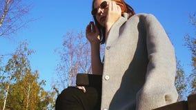 La ragazza teenager in un cappotto grigio mette sopra gli occhiali da sole ed i sorrisi un giorno soleggiato stock footage