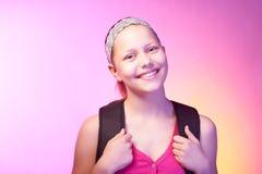 La ragazza teenager va a scuola con uno zaino su lei indietro Immagine Stock Libera da Diritti