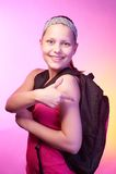 La ragazza teenager va a scuola con uno zaino su lei indietro Immagini Stock