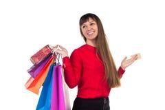 La ragazza tiene la carta di credito di attività bancarie, sacchi di carta colourful di acquisto Fotografie Stock