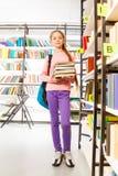 La ragazza tiene i libri e sta lo scaffale vicino in biblioteca Fotografia Stock