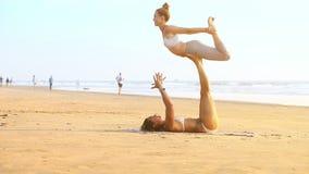 La ragazza tiene il partner sulla posa allungata di yoga delle gambe sulla spiaggia video d archivio