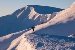 La ragazza tiene il suo snowboard sopra se stessa nelle montagne nell'inverno Immagine Stock Libera da Diritti
