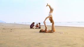 La ragazza tiene l'amico sulle gambe in testa di posa di yoga giù sulla spiaggia archivi video