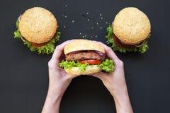 La ragazza tiene l'hamburger americano fresco Fondo scuro fotografia stock libera da diritti