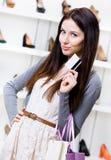 La ragazza tiene la carta di credito nel negozio delle calzature Immagine Stock Libera da Diritti