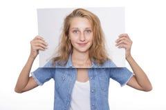 La ragazza tiene la sua immagine davanti al suo fronte Immagine Stock Libera da Diritti