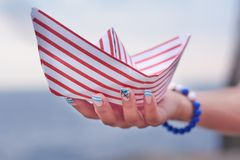 La ragazza tiene la nave del Libro Bianco con le linee rosse sulla sua mano Immagine Stock Libera da Diritti