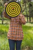 La ragazza tiene nel bersaglio delle mani con la freccia nell'obiettivo concentrare fuori nel parco fotografie stock