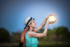 La ragazza tiene nelle mani che la luna è un modo favoloso Immagini Stock Libere da Diritti