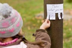 La ragazza tiene per l'annuncio scritto a mano Immagine Stock