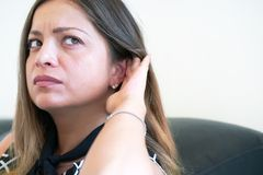 La ragazza tiene la sua mano vicino all'orecchio fotografie stock libere da diritti