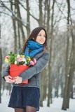 La ragazza tiene in suo contenitore di regalo rosso delle mani con i bei fiori del mazzo come regalo per il giorno del ` s delle  Fotografia Stock Libera da Diritti
