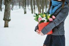 La ragazza tiene in suo contenitore di regalo rosso delle mani con i bei fiori del mazzo come regalo per il giorno del ` s delle  Immagini Stock Libere da Diritti