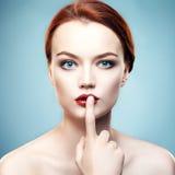La ragazza tiene un dito vicino alle labbra Immagini Stock