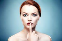 La ragazza tiene un dito vicino alle labbra Fotografia Stock