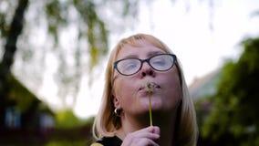 La ragazza tiene un fiore del dente di leone davanti al suo e scarica i semi bianchi Meravigliosamente sono sparsi ai lati beau video d archivio
