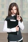 La ragazza tiene una cartella e mette una mano con la penna alla sua bocca Fotografie Stock