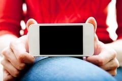 La ragazza tiene uno smartphone in mani Immagini Stock