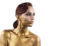 La ragazza tinta in oro, isolato su un fondo bianco Fotografia Stock
