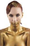 La ragazza tinta in oro, isolato su un fondo bianco Fotografie Stock Libere da Diritti
