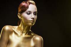 La ragazza tinta in oro su un fondo nero Fotografie Stock