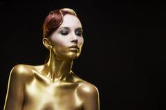 La ragazza tinta in oro su un fondo nero Fotografie Stock Libere da Diritti