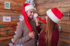La ragazza tocca il tipo con una palla dal cappello del ` s del nuovo anno fotografia stock libera da diritti