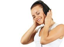 La ragazza in trasduttore auricolare ascolta musica con l'occhio chiuso Fotografia Stock