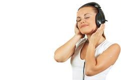La ragazza in trasduttore auricolare ascolta musica con l'occhio chiuso Fotografia Stock Libera da Diritti