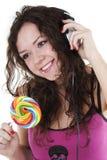 La ragazza in trasduttori auricolari balla e mangia un lollipop Immagine Stock Libera da Diritti