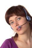 La ragazza in trasduttori auricolari comunica con microfono Immagine Stock