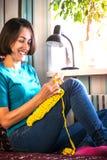 La ragazza tricotta lavora all'uncinetto a casa Donna impegnata in cucito Una magliaia si siede su un sofà e sugli impianti Hobby immagini stock