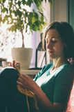 La ragazza tricotta lavora all'uncinetto a casa Donna impegnata in cucito Una magliaia si siede su un sofà e sugli impianti Hobby fotografia stock
