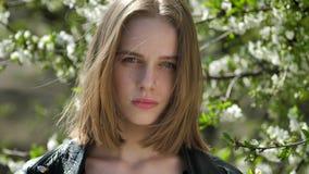 La ragazza triste giovane sta guardando intorno in parco di giorno di estate, il concetto di pensiero, albero della fioritura su  video d archivio