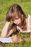 La ragazza triste sta trovandosi su erba verde Fotografia Stock