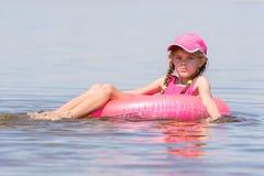 La ragazza triste in un cappuccio che galleggia nel fiume si è seduta sul cerchio di nuoto Fotografie Stock Libere da Diritti