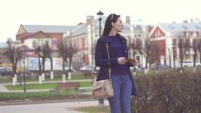 La ragazza trova sulla via un portafoglio perso con soldi ed i documenti stock footage