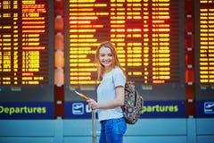La ragazza turistica con lo zaino e continua i bagagli in aeroporto internazionale, vicino al bordo di informazioni di volo Fotografia Stock