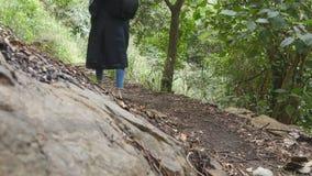 La ragazza turistica con lo zaino sta camminando lungo i piedi femminili della foresta tropicale che fa un passo alla traccia al  video d archivio