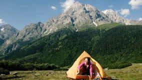 La ragazza turistica felice sveglia, solleva le mani su, apre la tenda e guarda fuori sui precedenti di un'alta montagna in a archivi video